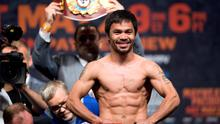 WBO welterweight champion Manny Pacquiao of the Philippines poses on the scale during an official weigh-in at the MGM Grand Garden Arena in Las Vegas