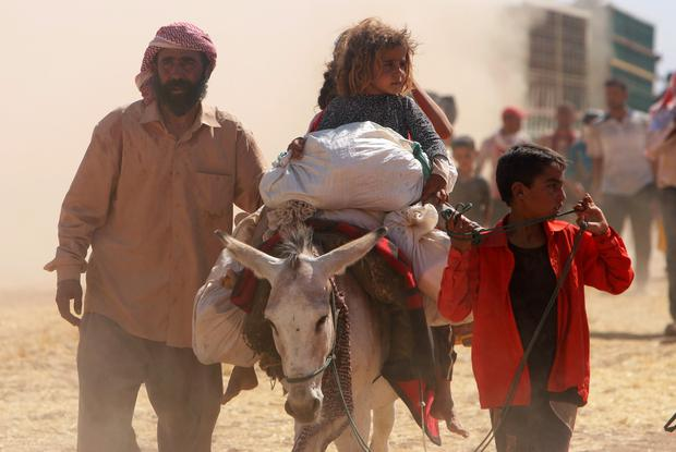 Displaced people from the minority Yazidi sect, fleeing violence from forces loyal to the Islamic State in Sinjar town, walk towards the Syrian border as others ride on a donkey on the outskirts of Sinjar mountain, near the Syrian border town of Elierbeh of Al-Hasakah Governorate
