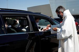 A priest wearing a face mask hands a host to a person sitting in a car as they celebrate France's first ever drive-in mass in Chalons en Champagne, after the country began a gradual end to the nationwide lockdown following the coronavirus disease (COVID-19) outbreak, near Reims, France, May 17, 2020. REUTERS/Gonzalo Fuentes