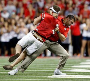 Ohio State assistant coach Anthony Schlegel tackles the pitch invader last night.