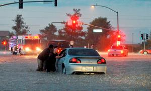 Bystanders help move a stranded motorist near Bear Valley Outerhighway South, Tuesday, Sept. 8, 2015, in Hesperia, Calif. The National Weather Service issued a flash flood warning and severe thunderstorm warning for the area on Tuesday night. (David Pardo/The Victor Valley Daily Press via AP) MANDATORY CREDIT