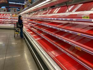 FILE PHOTO: A shopper picks over the few items remaining in the meat section, as people stock up on supplies amid coronavirus fears, at an Austin, Texas, grocery store on March 13, 2020. REUTERS/Brad Brooks/File Photo