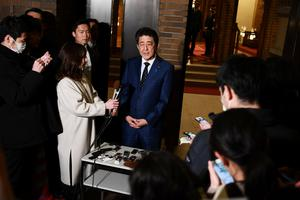 Japan's Prime Minister Shinzo Abe talks to the journalists in front of the prime minister's residence in Tokyo, Japan on Tuesday March 24 after a phone call with IOC President Thomas Bach on postponing the Olympic Games amid growing concerns over the coronavirus. Charly Triballeau/Pool via REUTERS