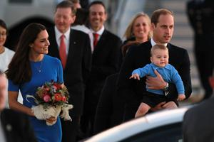 Catherine Duchess of Cambridge walks with Prince William, Duke of Cambridge carrying Prince George of Cambridge as the Royal Family arrive at Fairbairn Airport