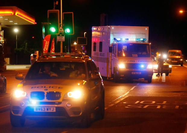 Police escort a Royal Armed Forces (RAF) ambulance carrying a British man infected with the Ebola virus after he was flown home on a C17 plane from Sierra Leone, at Northolt air base outside London