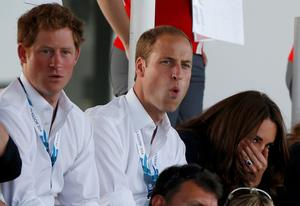 Catherine (R), Duchess of Cambridge, sits with her husband Prince William (C), and Britain's Prince Harry as they react watching hockey at the 2014 Commonwealth Games in Glasgow
