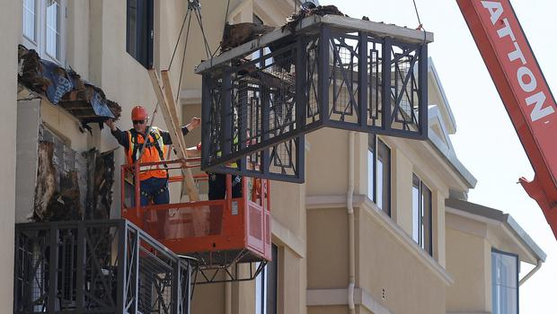 Workers remove the fourth floor balcony at the apartment complex in Berkeley. Photo: AP