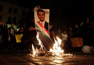 A demonstrator burns a photograph of Mexico's President Enrique Pena Nieto during a protest in support of the 43 missing Ayotzinapa students. Thousands took to the streets across Mexico protesting over President Enrique Pena Nieto's handling of the apparent massacre of the trainee school teachers after their abduction (REUTERS/Daniel Becerril)