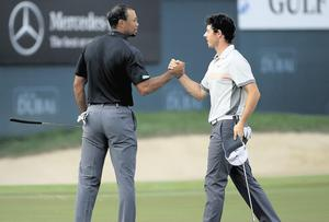 Tiger Woods and Rory McIlroy shake hands at the end of the second round of the Dubai Desert Classic