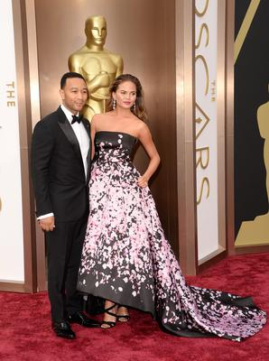 Recording artist John Legend (L) and model Christine Teigen attend the Oscars held at Hollywood & Highland Center on March 2, 2014 in Hollywood, California.  (Photo by Jason Merritt/Getty Images)