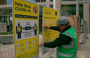 Covid 19 compliance officer John Gaskin puts up social distancing signs on a building site in Dublin's city centre, ahead of phase one of the road map which will allow builders to go back to work. Photo:Gareth Chaney/Collins