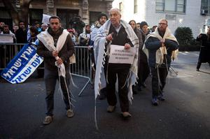Rabbi Avi Weiss (C) bypasses a barricade to cross the street to place a sign on the door of the Palestine Mission to the United Nations in New York, as demonstrators rally over a deadly attack on a Jerusalem synagogue, November 18, 2014. Two Palestinian men armed with meat cleavers and a gun entered the synagogue in a quiet ultra-Orthodox neighborhood during morning prayers on Tuesday and attacked around 25 worshippers, killing four and wounding eight, several seriously. Three of the victims held dual U.S.-Israeli citizenship.  REUTERS/Carlo Allegri