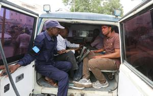 Somali Freelance journalist Mohamed Guray sits in a police ambulance after he was injured in a secondary explosion in front of Dayah hotel in Somalia's capital Mogadishu, January 25, 2017. REUTERS/Feisal Omar
