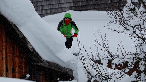A woman sweeps heavy snow from her roof in Austria. Photo: Reuters