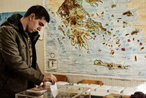A voter casts his ballot in front of a map of Greece at a polling station in Athens. Photo: Milos Bicanski/Getty Images