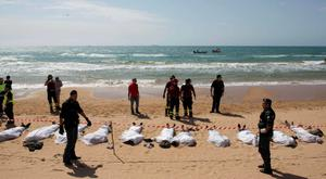 Rescue workers stand next to bodies of migrants who drowned on the beach in the Sicilian village of Sampieri September 30, 2013. At least 13 people on a migrant boat arriving in Sicily drowned close to the coast near the eastern city of Ragusa, apparently after trying to disembark from their stranded vessel, Italian authorities said on Monday. Officials said the boat was carrying around 250 people but there was no immediate word on where they came from.  REUTERS/Gianni Mania (ITALY - Tags: DISASTER TPX IMAGES OF THE DAY)