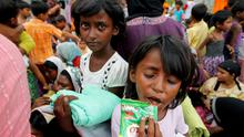 A Rohingya migrant child, who recently arrived in Indonesia by boat, eats chocolate while queuing up with others for immigration identification purposes inside a temporary compound for refugees in Aceh Timur regency (REUTERS/Beawiharta)