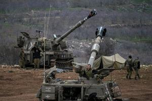 Israeli soldiers are seen next to mobile artillery units near the border with Syria in the Golan Heights