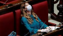 Taking precautions: Deputy Maria Teresa Baldini wears a protective mask and gloves inside the lower house parliament building in Italy. Photo: REUTERS/Remo Casilli