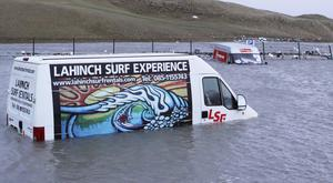 Two vans lie in several feet of water in the promenade carpark at Lahinch in Co Clare. Photo: Press 22