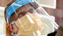 A staff member at a pharmacy in Holywood, Co. Down, is pictured wearing a protective visor and face mask. Photo: REUTERS/Jason Cairnduff