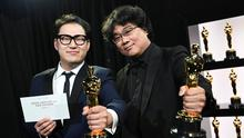 """Bong Joon Ho and Han Jin Won hold their Oscar statues for Original Screenplay for """"Parasite"""" at the 92nd Academy Awards in Hollywood, Los Angeles, California, U.S., February 9, 2020. Matt Petit/A.M.P.A.S./Handout via REUTERS ATTENTION EDITORS. T"""