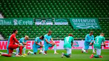 Werder Bremen and Wolfsburg players take a knee in protest at the killing of George Floyd before Bremen's 1-0 defeat which pushed them closer to relegation from the Bundesliga. Photo by Patrik Stollarz/Pool via Getty Images