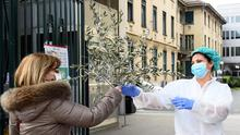 Tribute: A nurse from the Molinette Hospital accepts a bunch of palm tree branches from a woman entering the premises on Palm Sunday in Turin. Photo: REUTERS/Massimo Pinca
