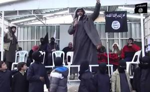 Armed men watch on as children who are thought to be 'graduating' from the Isis school stand in the foreground