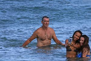 Pierce Brosnan unknowingly photobombed girls at the beach. Picture: Splash