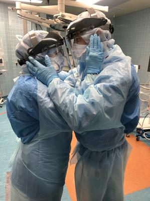 Love: Husband and wife Mindy Brock and Ben Cayer, who are nurses at Tampa General Hospital in Florida, give each other a reassuring embrace in full protective gear before their shift on a coronavirus team. The photo was taken by chief nurse anaesthetist Nicole Hubbard in recent weeks and posted on Facebook, where it went viral. Picture: AP
