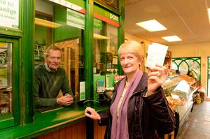 Ventry postmaster Seamus Ó Luing with customer Maire Ui Chiobhain in Ceann Trá post office. Photo: Don MacMonagle