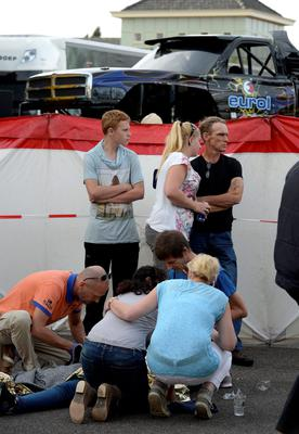 Paramedics attend to the wounded at a monster truck festival in Haaksbergen September 28, 2014. Three people were killed, including a child, when a giant pick-up truck (pictured at back) spun out of control while attempting to perform a stunt demonstration in the Dutch city of Haaksbergen on Sunday, Dutch public television quoted the local mayor as saying
