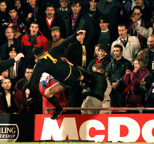 Eric Cantona launches himself at Crystal Palace fan Matthew Simmons after being sent off on this day in 1995. Photo: Action Images