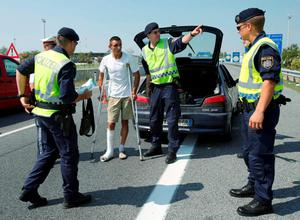 Austrian police officers speak to a man at a checkpoint in the village of Nickelsdorf, Austria, August 31, 2015.  REUTERS/Heinz-Peter Bader