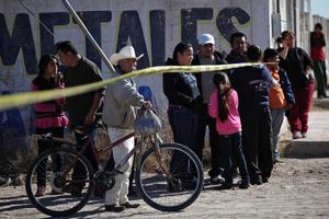Onlookers stand near the police cordon at a crime scene where a man was gunned down by unknown assailants in Ciudad Juarez