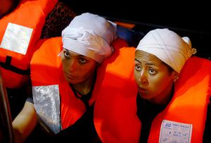 Migrants sit in a Migrant Offshore Aid Station (MOAS) RHIB alongside the MOAS ship MV Phoenix before being transferred to the Norwegian ship Siem Pilot off the coast of Libya