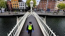 Garda Lorcan Cassidy crosses a deserted Ha'penny bridge in Dublin as he patrols the deserted city centre streets. Picture; Gerry Mooney