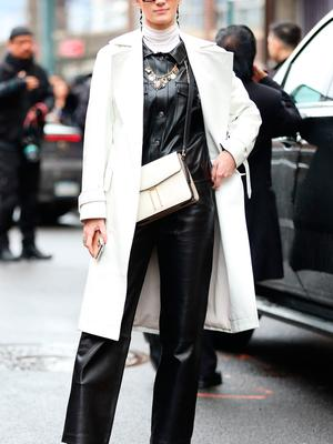 A guest is seen wearing a white coat, white turtleneck, black pants suit with white purse and white heels outside of the Coach 1941 show during New York Fashion Week on February 11, 2020 in New York City. (Photo by Donell Woodson/Getty Images)