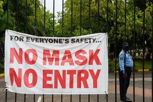 A private security guard stands beside a banner with at entrance gate of the English and Foreign Languages University (EFL) in Secunderabad. (Photo by NOAH SEELAM/AFP via Getty Images)