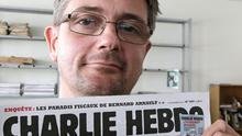 n this Sept.19, 2012 file photo, Stephane Charbonnier also known as Charb , the publishing director of the satyric weekly Charlie Hebdo, displays the front page of the newspaper