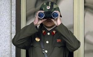 A North Korean soldier looks at the southern side through a pair of binoculars at the border village of Panmunjom, which has separated the two Koreas since the Korean War, in Paju, north of Seoul, South Korea