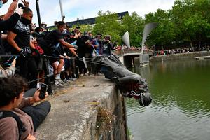 The statue of Edward Colston is toppled into Bristol Harbour. Photo: Ben Birchall/PA Wire