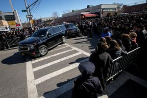 Mourners watch cars carry the remains of  of seven children killed in a Brooklyn fire in New York March 22, 2015. REUTERS/Brendan McDermid