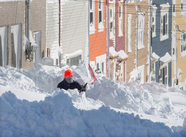 A resident digs out his walkway in St. John's Newfoundland on Saturday, Jan. 18, 2020. The state of emergency ordered by the City of St. John's is still in place, leaving businesses closed and vehicles off the roads in the aftermath of the major winter storm that hit the Newfoundland and Labrador capital. (Andrew Vaughan/The Canadian Press via AP)