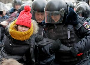 Police detain a protester outside a courthouse in Moscow February 24, 2014. Seven opponents of President Vladimir Putin were sentenced to prison terms ranging from two and a half to four years on Monday over a demonstration that turned violent, and riot police detained over 100 people protesting outside the court