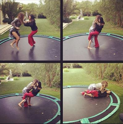In the sequence of four snaps, the pair can be seen bouncing together before Kylie falls back in pain on to the trampoline.  (Instagram/ Khloe Kardashian)