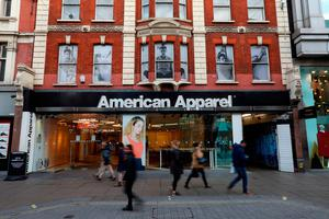 Shoppers pass a closed down American Apparel shop on Oxford Street in London. Photo: Bloomberg