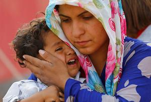 A mother comforts her distressed child after crossing into Turkey from Syria to escape Isil