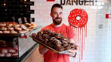 John Brennan with a tray of 'Banoffee Autopsy' doughnuts. Photo: Fran Veale